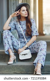 Outdoor full body portrait of young beautiful fashionable woman posing in street, sitting on stairs. Model wearing stylish gray boater hat, jumpsuit with flower print, carries small white bag