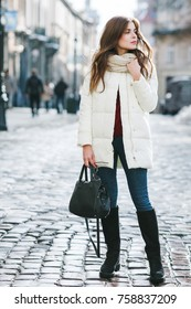 Outdoor full body portrait of young beautiful fashionable woman wearing stylish white winter puffer coat, suede high boots, holding bag. Model posing in street of the city. Female fashion concept