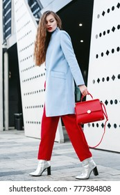 Outdoor full body portrait of young beautiful fashionable woman walking in street. Model wearing light blue coat, red pants, silvery ankle boots, holding trapeze handbag. Female fashion concept