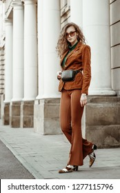 Outdoor full length fashion portrait of young confident woman wearing brown corduroy blazer, wide trousers, leather belt bag, leopard print sunglasses, cowboy boots, walking in street of european city