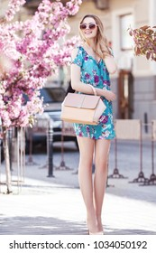 Outdoor fullbody portrait of young beautiful fashionable girl walking in street of european city. Model wearing stylish spring dress sunglasses, holding pink handbag. Spring, summer  fashion