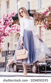 Outdoor fullbody portrait of young beautiful fashionable girl walking in street of european city. Model wearing stylish short dress, sunglasses, holding pink handbag. Spring, summer fashion concept
