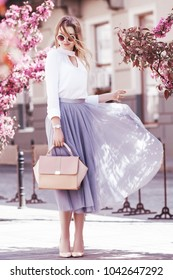 Outdoor fullbody portrait of young beautiful fashionable girl walking in street of european city. Model wearing stylish blouse, skirt, sunglasses, holding pink handbag. Spring, summer  fashion