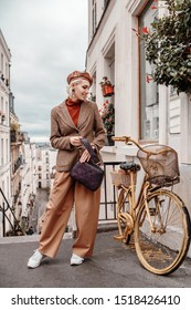 Outdoor full-length autumn portrait of young happy smiling fashionable lady wearing trendy leather beret, beige checkered blazer, wide trousers, white sneakers, holding bag, posing in Parisian street