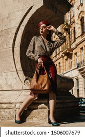 Outdoor full-length fashion portrait of elegant, luxury woman wearing trendy leather midi skirt, beret, snakeskin print blouse, shoes, sunglasses, holding brown bag, posing in street of European city