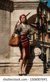 Outdoor full-length fashion portrait of elegant, luxury woman wearing trendy leather dark red pencil midi skirt, beret, snakeskin print blouse, shoes, sunglasses, holding brown bag, posing in street