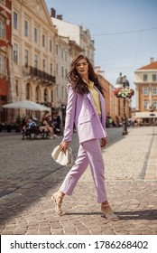 Outdoor full-length fashion portrait of elegant woman wearing lilac suit: blazer, trousers, strap sandals, holding trendy big white leather pouch handbag, walking in street of European city