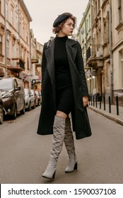 Outdoor full-length fashion portrait of young elegant woman wearing classic black coat, short turtleneck dress, gray suede high, over knee boots, beret, walking in street of European city