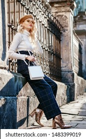 Outdoor full-length portrait of fashionable blonde woman wearing stylish autumn outfit: beige beret, glasses, white turtleneck, checkered high waist trousers, golden ankle boots, heels, holding bag