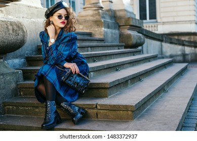 Outdoor full-length portrait of pretty curly lady wearing trendy autumn checkered dress, leather beret, glasses, wrist watch, black tights, boots, holding small bag, posing in street. Copy space