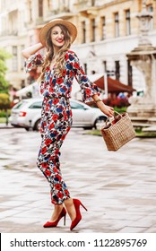 Outdoor full-length portrait of yong beautiful happy smiling woman wearing stylish jumpsuit with floral print, hat, red shoes, holding straw bag. Model walking in street of european city