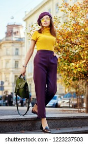 Outdoor full-length portrait of young fashionable woman wearing purple beret, trousers, yellow glasses, turtleneck, loafers, wrist watch, holding green leather handbag, posing in autumn street of city