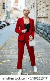 Outdoor full-length street fashion portrait of young blonde woman wearing total red look, suit, blazer and trousers, white sneakers, with leather shoulder bag. Model posing in European city. Autumn