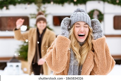Outdoor Fun. Happy Cheerful Young Couple Throwing Snowballs At Each Other, Having Fun During Winter Date At Camping, Enjoying Spending Holidays Together, Selective Focus At Laughing Blonde Girlfriend