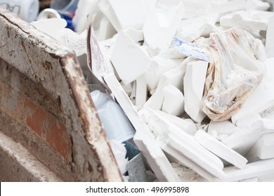 Outdoor garbage container filled with white plastic bags
