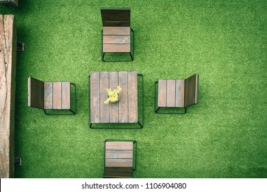 Outdoor gardening design. Top view of wooden chairs and table on green artificial grass in vintage style. (Selective focus)