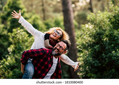 Outdoor happy and cheerful caucasian couple with glasses have fun and enjoy the nature and leisure activity together - man carry woman and both laugh a lot
