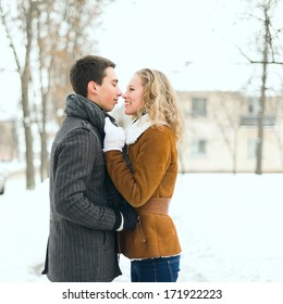Outdoor happy couple in love posing in cold winter weather. Young man and woman having fun outdoor in winter