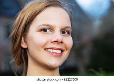 Outdoor head portrait of pretty young smiling woman
