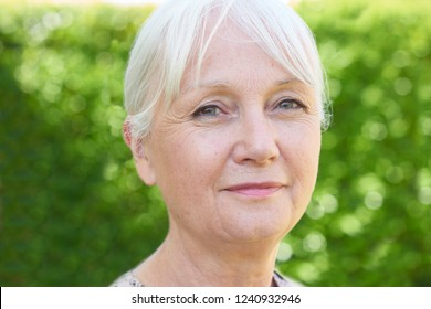 Outdoor Head And Shoulders Portrait Of Serious Senior Woman