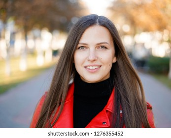 Outdoor headshot of 20s year stylish brunette woman in red leather coat on lunch break drinking coffee or tea to go. Autumn urban background.