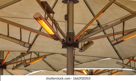 Outdoor heating infrared lamps under umbrella in street cafe in cold season (winter, autumn or spring)