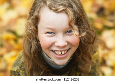Outdoor high angle portrait of smiling blond girl in autumn park