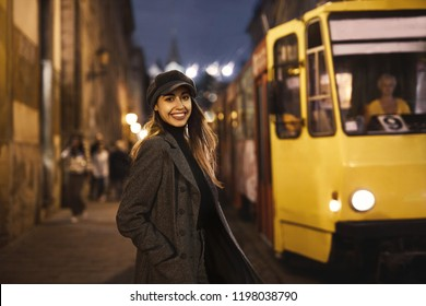 Outdoor horizontal portrait of young beautiful fashionable brunette woman posing on the evening street in old city of Lviv at autumn with a tram on background . Model wearing stylish gray coat, skinny