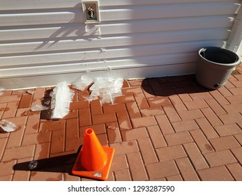 outdoor hose spigot with melting ice and red bricks in winter