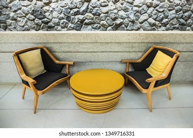 Outdoor hotel reception area modern chairs and table with background of rock wall