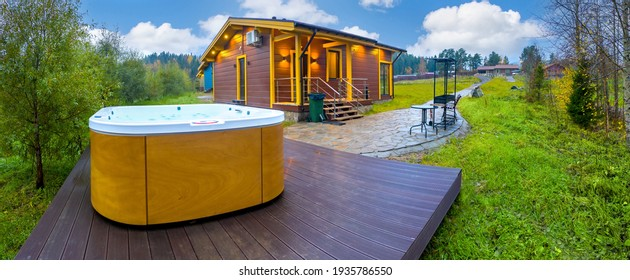 Outdoor hydromassage pool. Panorama of a cottage with a spa bath. Hydromassage pool on a wooden pedestal. Concept - sale of swimming pools. Landscape with country cottage. Swimming pool with massage