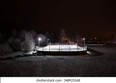 Outdoor ice skating rink lit up at night with Christmas lights in the background