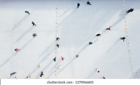 Outdoor ice skating rink with people riding on a winter day. Aerial view from the drone.
