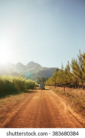 Outdoor image of distant car approaching on a rural dirt road on a sunny day. Automobile driving through the country road.