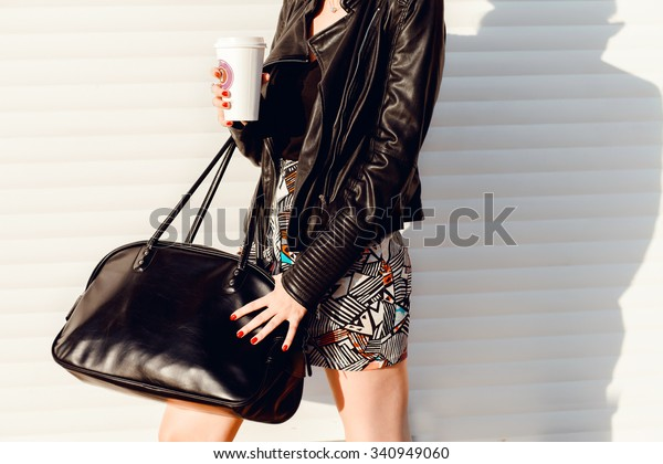 outdoor image of stylish woman with total black outfit,leather suit,trendy coat,fall fashion bag,girl resting and drinking tea sitting in autumn garden on the steps, wrapped in a woolen plaid blanket.