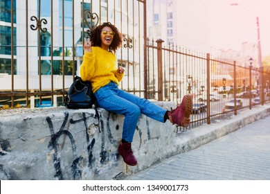 Outdoor image of young attractive black woman with stylish Afro hairs  having fun  and sitting on  bridge  in modern district. Yellow glasses and pullover.
