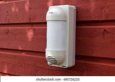 Outdoor infrared motion detector on the wooden wall