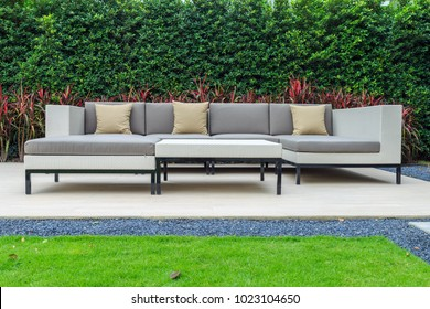 An outdoor interior picture of  brown pillows and gray cushion on a modern resin wicker sofa in the garden with nature background.