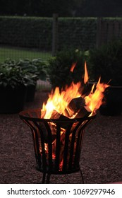 Outdoor iron firepit with burning wood logs