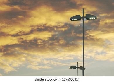 Outdoor Lamp Posts with LED Lights on Cloudy Sky Background at Twilight