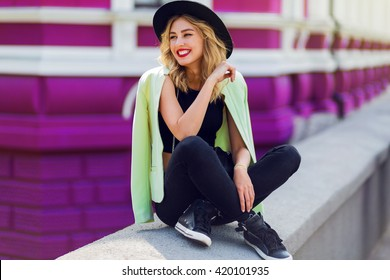 Outdoor lifestyle  close up portrait of happy blonde young woman in stylish  casual outfit sitting on bridge on the street. Pretty hipster girl having fun and enjoying  holidays.