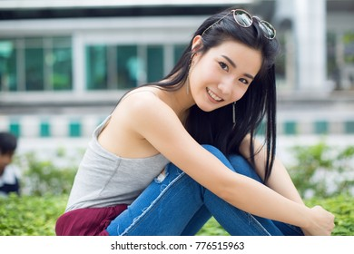 Outdoor lifestyle close up portrait of happy young woman in stylish casual outfit sitting on the street. Pretty hipster girl having fun and enjoying holidays.