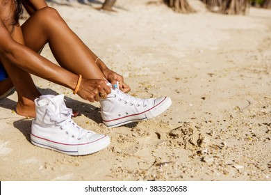 Outdoor lifestyle close-up of the legs of black beautiful teenage girl. Young hipster woman tying laces in her white sneakers. Sunny hot summer day at tropical seashore.
