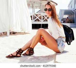 Outdoor lifestyle closeup summer portrait of happy young brunette girl having fun outdoor with ling tanned legs