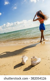 Outdoor lifestyle close-up of white sneakers at tropical seashore. Silhouette of sporty black beautiful teenage girl with long legs on a background. Young hipster woman, sunny hot summer day.