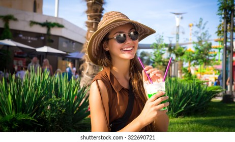 Outdoor lifestyle fashion portrait of Stylish hipster young woman in trendy sunglasses with smoothie  cocktai  in city park outdoor against bright color urban background .Smile,Happy,positive emotions