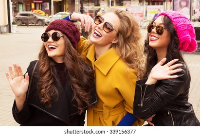Outdoor lifestyle fashion portrait of three pretty cheerful girls friends, smiling and having  fun. Waving to someone. Walking on the autumn city. Wearing stylish bright outerwear, hats and sunglasses