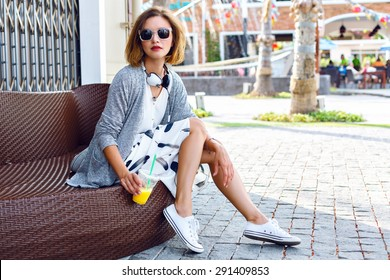 Outdoor lifestyle fashion portrait of woman posing on the street drinking orange smoothie, wearing stylish midi skirt, cardigan and sunglasses, joy, relax, vacation, travel.