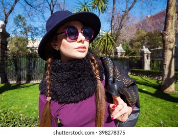 Outdoor lifestyle fashion portrait young stylish lady wearing trendy spring outfit, black hat,leather coat,scarf.Model wearing stylish wide-brimmed hat.Girl looking at camera. Female fashion.Toned