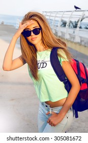 Outdoor lifestyle hipster teen girl posing alone at city center, long amazing hairs, pretty smile, bright make up, travel in Europe with backpack, showing yo science. Warm vintage bright colors.
